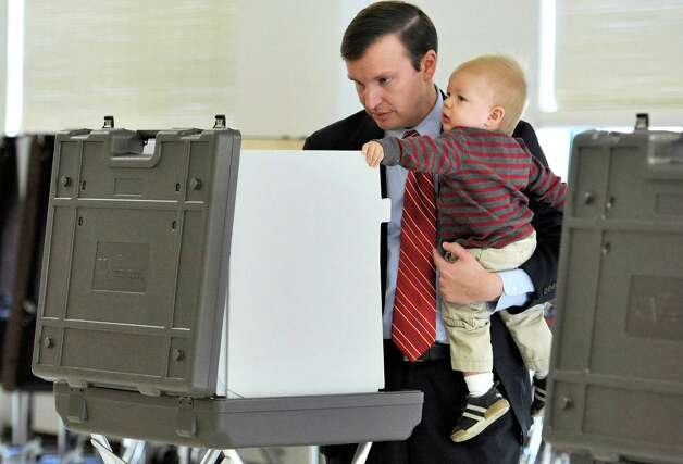 Democratic candidate for U.S. Senate Chris Murphy votes while holding son Rider in Cheshire, Conn., Tuesday, Nov. 6, 2012.  Murphy and Republican opponent Linda McMahon are vying for the Senate seat now held by Joe Lieberman, an independent who's retiring. Photo: Jessica Hill, AP Photo/Jessica Hill / Associated Press