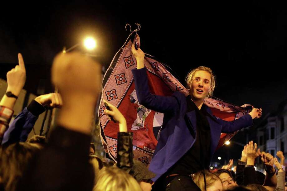 A young woman drapes an Obama flag over herself while perched on a friend's shoulders on election night Tuesday, November 6, 2012, on Capitol Hill in Seattle, Wash. Crowds took to the streets after President Barack Obama's projected reelection. Referendum 74 and I-502 also passed in Washington state. Photo: JORDAN STEAD / THE EMERALD COLLECTIVE / FOR SEATTLEPI.COM
