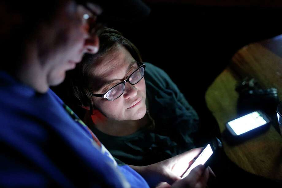 Husband Scott Massey, left, and wife Carrie Siber-Massey, right, anxiously check polling results on their phones on election night on Tuesday, November 6, 2012, at Neumos on Capitol Hill in Seattle, Wash. Crowds flocked to return parties hosted by a number of bars in the area to wait out final ballot results. In addition to President Barack Obama's reelection, Referendum 74 and I-502 were both passed in Washington state. Photo: JORDAN STEAD / THE EMERALD COLLECTIVE / FOR SEATTLEPI.COM