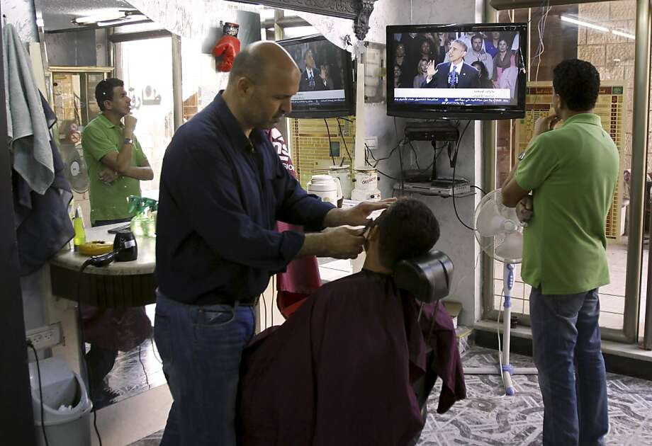 Palestinians at a barber shop watch a televised speech by U.S. President Barack Obama after his vicotry, in the West Bank town of Jenin, Wednesday, Nov. 7, 2012. Photo: Mohammed Ballas, Associated Press