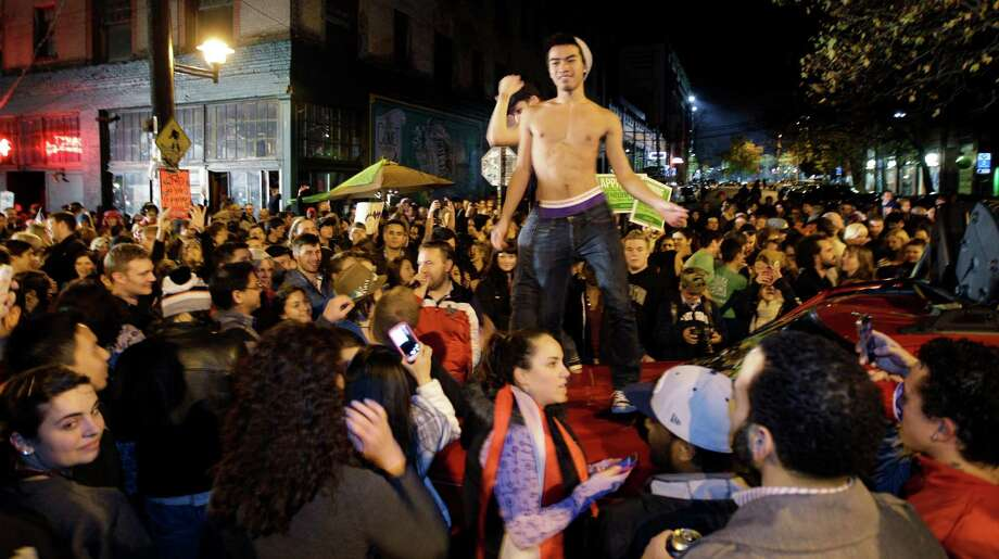 Two men dance as they stand on a car during a street celebration of early election returns favoring Washington state Referendum 74, which would legalize gay marriage, during a large impromptu street gathering in Seattle's Capitol Hill neighborhood, Tuesday, Nov. 6, 2012. The re-election of President Barack Obama and Referendum 74 drew the most supporters to the streets. Photo: TED S. WARREN / ASSOCIATED PRESS