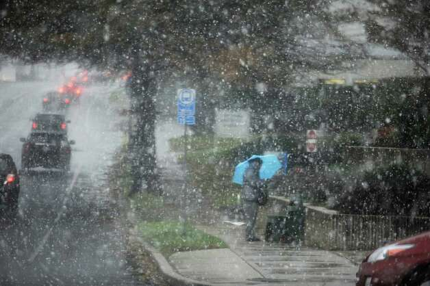 A woman waits for the bus in the snow, during the Nor'easter on East Putnam, Greenwich Conn., Wednesday, Nov. 7, 2012. Photo: Helen Neafsey / Greenwich Time