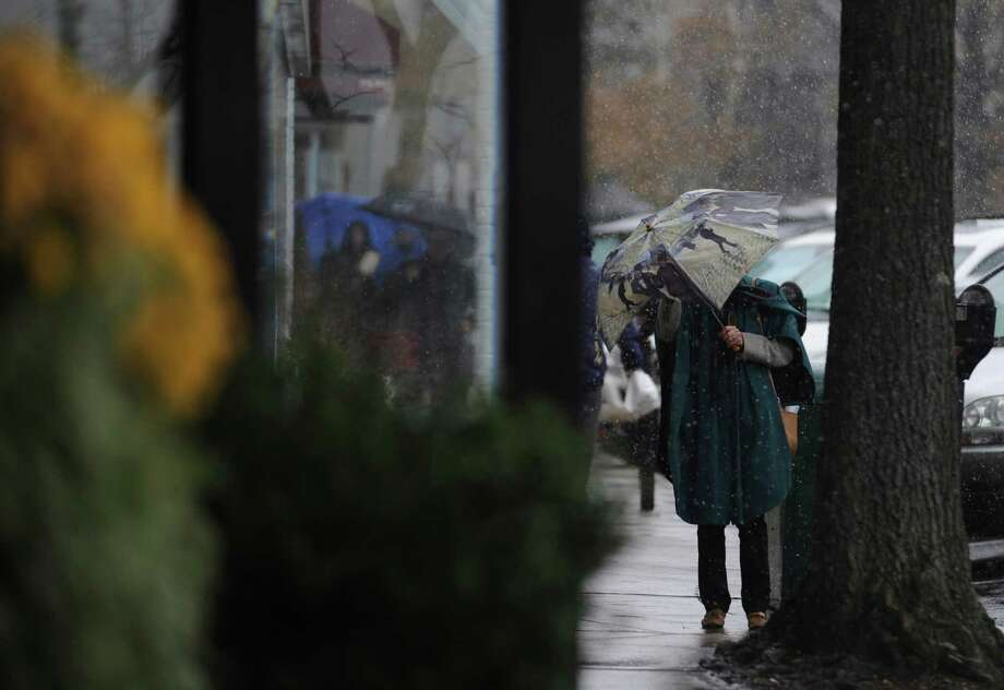 A woman walks with an umbrella in the snow on Greenwich Avenue during the Nor'easter, in Greenwich, Conn., Wednesday, Nov. 7, 2012. Photo: Helen Neafsey / Greenwich Time