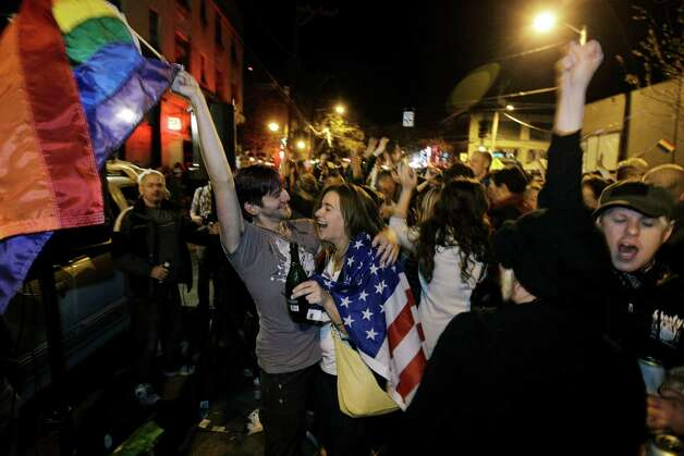 Revelers display U.S. and gay pride flags as they celebrate early election returns favoring Washington state Referendum 74, which would legalize gay marriage, during a large impromptu street gathering in Seattle's Capitol Hill neighborhood, in the early hours of Wednesday, Nov. 7, 2012. The re-election of President Barack Obama and Referendum 74 drew the most supporters to the streets. Photo: TED S. WARREN / ASSOCIATED PR