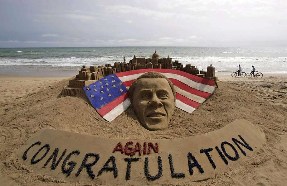 Cyclists ride on a beach passing by a sand sculpture congratulating U.S. president Barack Obama for a second term in office in Puri, India, Wednesday, Nov. 7, 2012. Obama captured a second White House term, blunting a mighty challenge by Republican Mitt Romney as Americans voted for a leader they knew over a wealthy businessman they did not. Photo: Biswaranjan Rout, Associated Press