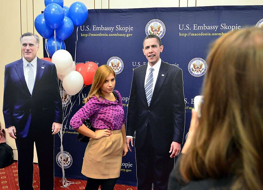 A young woman poses for a photo with a cutout of President Barack Obama, right, beside a cutout of Republican candidate Mitt Romney, left, during an election night event organized by the U.S. embassy in Skopje, Macedonia, early Wednesday, Nov.7, 2012. President Barack Obama won re-election Tuesday night despite a fierce challenge from Republican Mitt Romney. Photo: Boris Grdanoski, Associated Press