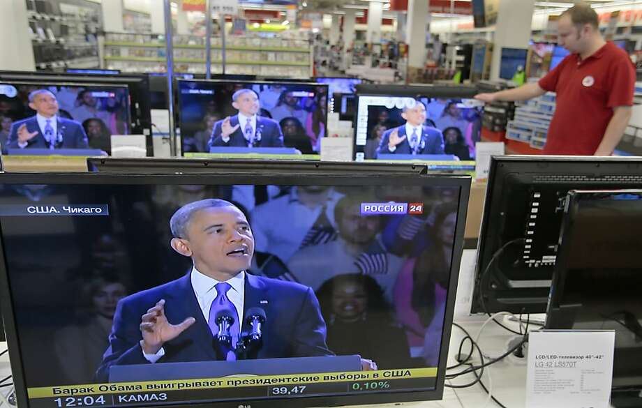A shop assistant watches US President Barack Obama speaking on TV screen in Moscow TV shop, Russia, Wednesday, Nov. 7, 2012. Obama defeated Republican challenger former Massachusetts Gov. Mitt Romney. Photo: Mikhail Metzel, Associated Press