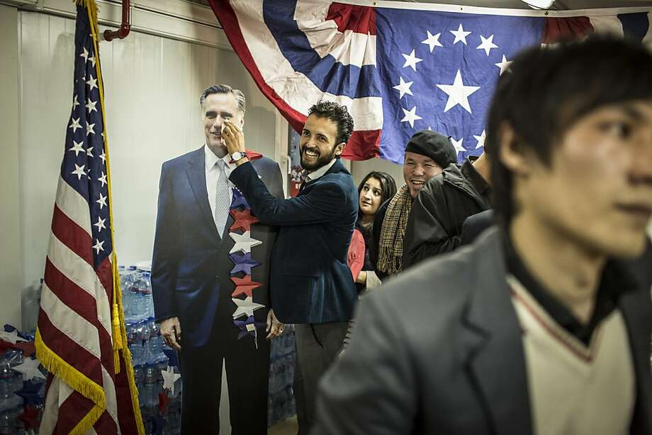 An Afghan journalist poses with a cardboard cut-out of Republican candidate Mitt Romney during a US 2012 presidential election watch event at the US embassy on November 7, 2012 in Kabul, Afghanistan. President Barack Obama won re-election against Republican candidate, former Massachusetts Governor Mitt Romney. Photo: Daniel Berehulak, Getty Images