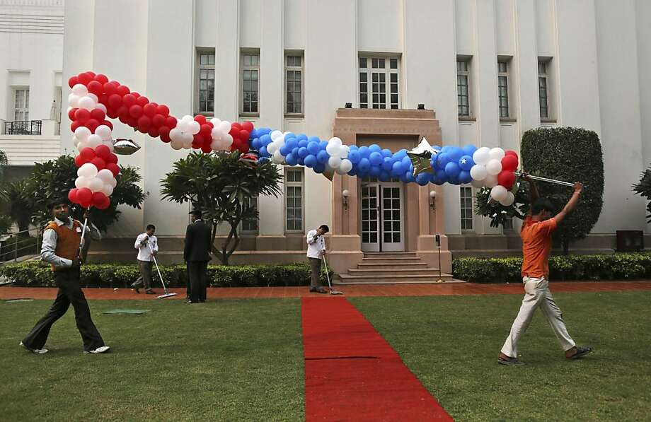 Indian workers carry colorful balloons after an event organized by the U.S embassy to mark the US elections at the landmark Imperial Hotel in New Delhi, India, Wednesday, Nov. 7, 2012. President Barack Obama captured a second White House term, blunting a mighty challenge by Republican Mitt Romney as Americans voted for a leader they knew over a wealthy businessman they did not. Photo: Kevin Frayer, Associated Press