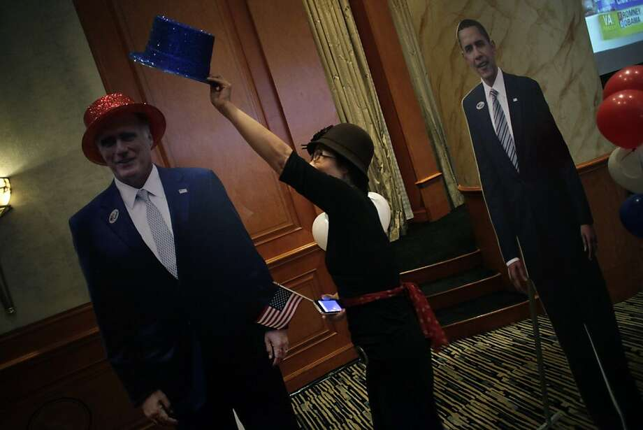 A guest places a blue hat, representing the Democratic Party, on to a cardboard cutout of Republican presidential candidate, former Massachusetts Gov. Mitt Romney after President Barack Obama's victory was announced, Wednesday, Nov. 7, 2012, in Shanghai, China.  Obama won re-election Tuesday night despite a fierce challenge from Republican Mitt Romney, prevailing in the face of a weak economy and high unemployment that encumbered his first term and crimped the middle class dreams of millions. Photo: Eugene Hoshiko, Associated Press
