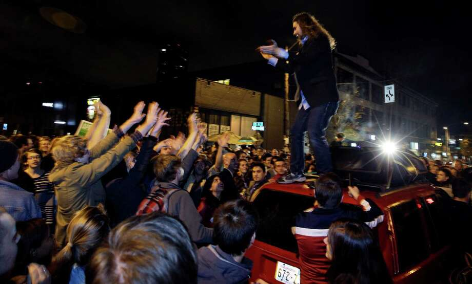 A man stands on a car and encourages a crowd gathered to celebrate the election results in Seattle's Capitol Hill neighborhood, Tuesday, Nov. 6, 2012. The re-election of President Barack Obama and Washington state's Referendum 74, which would legalize gay marriage, drew the most supporters to the streets. Photo: TED S. WARREN / ASSOCIATED PRESS