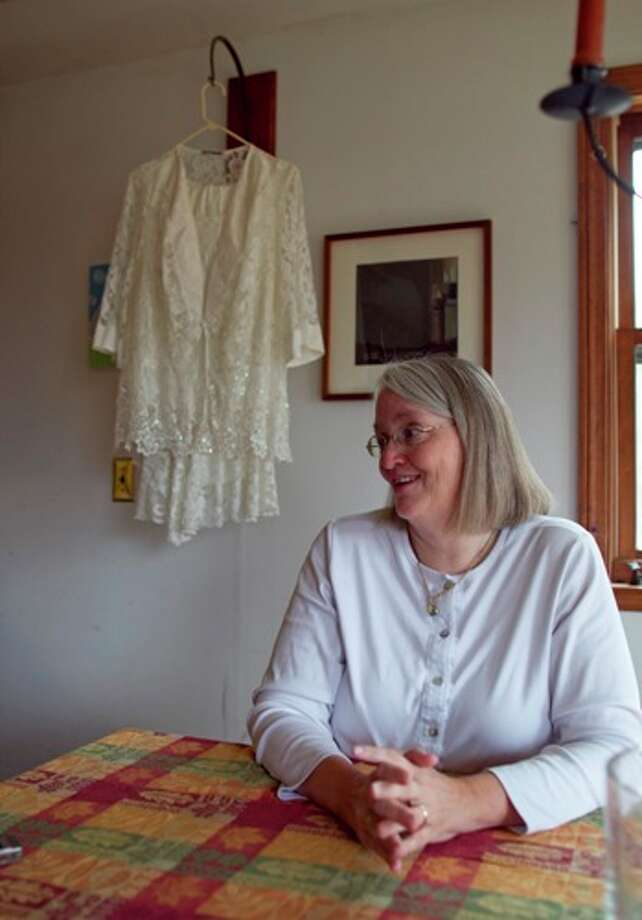 A wedding dress hangs behind Sarah Dowling at her home, Wednesday, Nov. 7, 2012, in Freeport, Maine.  Dowling plans to marry her partner of 18 years, now that Mainer's have legalized same-sex marriage. Photo: Robert F. Bukaty