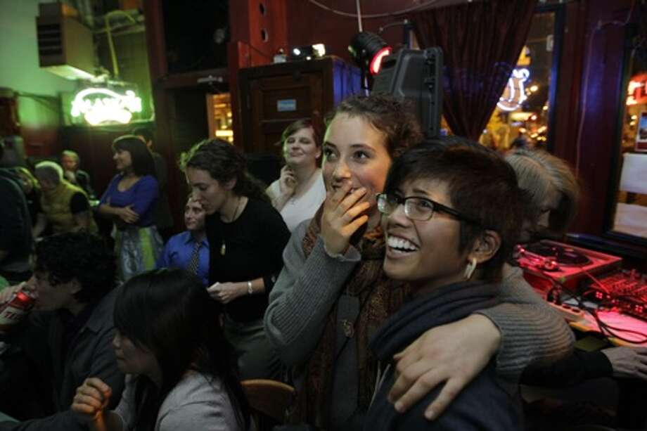 Christabel Escarez, right, and Daisy Frearson, second from right, watch early election results at the Wildrose bar in Seattle's Capitol Hill neighborhood Tuesday, Nov. 6, 2012. Both women said they were supporting Washington state's Referendum 74, which would legalize same-sex marriage. Photo: Ted S. Warren