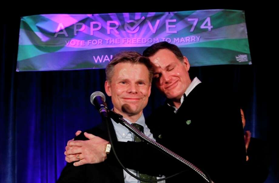 Rep. Jaime Pedersen, left, is embraced by his partner Eric Cochran Pedersen while speaking during an election watch party for proponents of Referendum 74, which would uphold the state's new same-sex marriage law, Tuesday, Nov. 6, 2012, in Seattle. Photo: Elaine Thompson