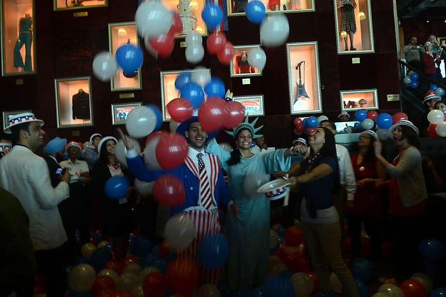 Guests and US citizens rejoice as the results of the US Presidential elections are announced during a US Election Returns party in Mumbai on November 7, 2012.  US President Barack Obama swept to re-election Tuesday, making history by overcoming a slow economic recovery and the high unemployment which haunted his first term to beat Republican Mitt Romney. Photo: Indranil Mukherjee, AFP/Getty Images