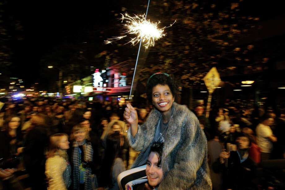 Crystal Davis, of Seattle, waves a sparkler as she celebrates the 2012 election with a large crowd in Seattle's Capitol Hill neighborhood, Tuesday, Nov. 6, 2012, in Seattle's Capitol Hill neighborhood. The re-election of President Barack Obama and Washington state's referendum 74, which would legalize gay marriage, drew the most supporters to the streets. Photo: TED S. WARREN / ASSOCIATED PRESS