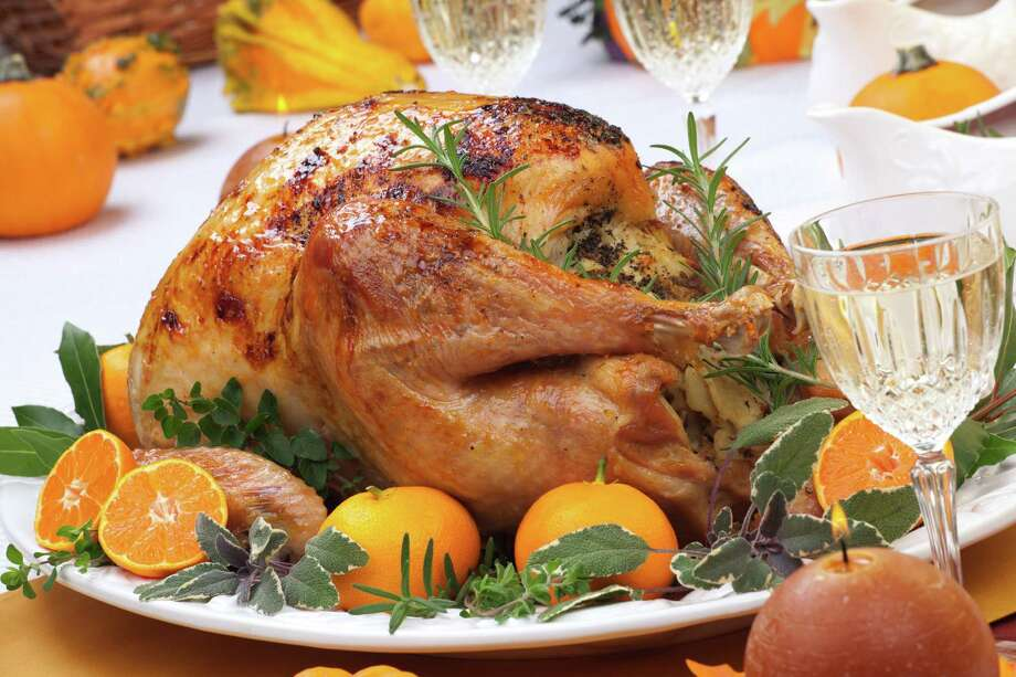 Garnished citrus glazed roasted turkey on holiday table, pumpkins, flowers, and white wine Photo: Bochkarev Photography / evgenyb - Fotolia