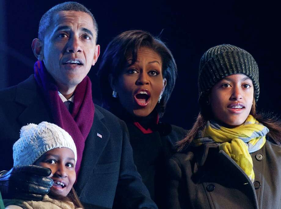 Sasha, Barack, Michelle and Malia Obama react as they push a button to light the National Christmas Tree during a ceremony on the Ellipse near the White House in Washington, D.C., Dec. 9, 2010. Photo: SAUL LOEB, AFP/Getty Images / 2010 AFP