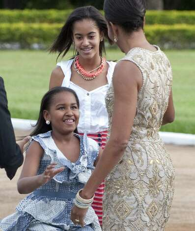Malia and Sasha Obama, greet their mother, First Lady Michelle Obama, after getting out of the motorcade upon arrival for a reception hosted by Brazilian President Dilma Rousseff at the Palacio do Alvorada, the official residence in Brasilia, Brazil, March 19, 2011. Photo: SAUL LOEB, AFP/Getty Images / 2011 AFP