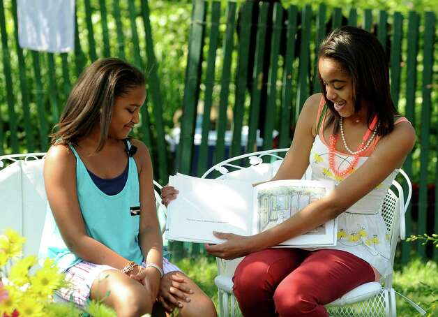 Sasha and Malia Obama read to children during the White House Easter Egg Roll on the South Lawn of the White House on April 25, 2011, in Washington, D.C. Photo: Getty Images