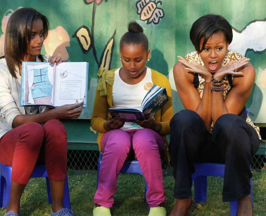 "Malia, Sasha and Michelle Obama take turns reading to children from ""The Cat in the Hat,"" by Dr. Seuss, as they visit the Emthonjeni Community Center in Zandspruit Township, Johannesburg, South Africa, on June 21, 2011. Photo: CHARLES DHARAPAK, AFP/Getty Images / 2011 AFP"
