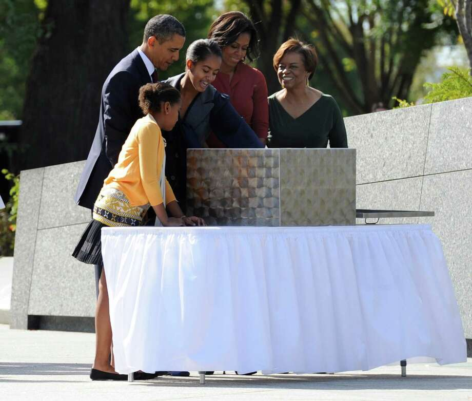 President Barack Obama, daughters Sasha and Malia, First Lady Michelle Obama and Michelle's mother, Marian Robinson, examine a time capsule as they arrive for the dedication of the Martin Luther King, Jr. Memorial on the National Mall Oct. 16, 2011 in Washington, D.C. Photo: Pool, Getty Images / 2011 Getty Images