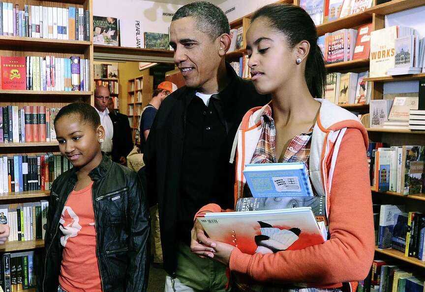 Sasha, Barack and Malia Obama shop for books at Kramerbooks and Afterwords, a local bookstore, in Wa