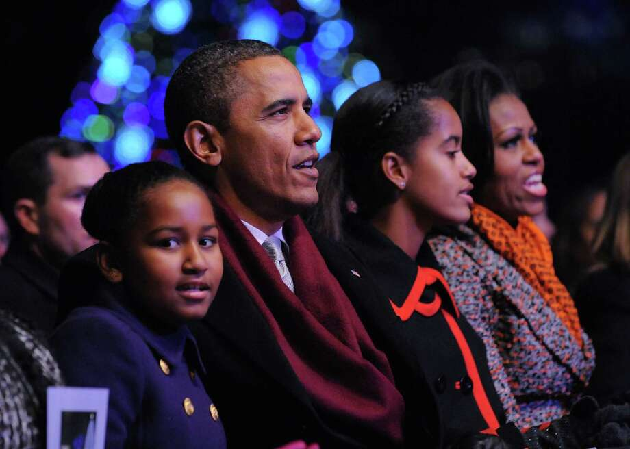 "Sasha, Barack, Malia and Michelle Obama sing ""Rudolf the Red Nose Reindeer"" during the annual lighting of the National Christmas tree on Dec. 1, 2011, at The Ellipse in Washington, D.C. Photo: MANDEL NGAN, AFP/Getty Images / 2011 AFP"