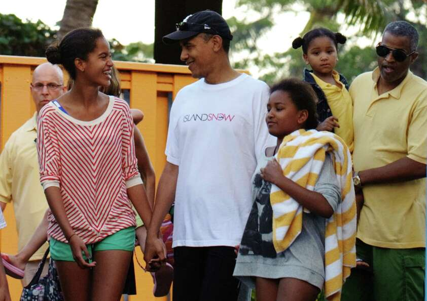 President Barack Obama walks with his daughters, Malia and Sasha, and friend Marty Nesbitt, to their