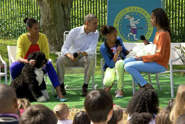 President Barack Obama and First Lady Michelle Obama listen as Malia and Sasha Obama read a book to children during the 2012 White House Easter Egg Roll on the South Lawn of the White House in Washington, D.C., April 9, 2012. Photo: JIM WATSON, AFP/Getty Images / 2012 AFP