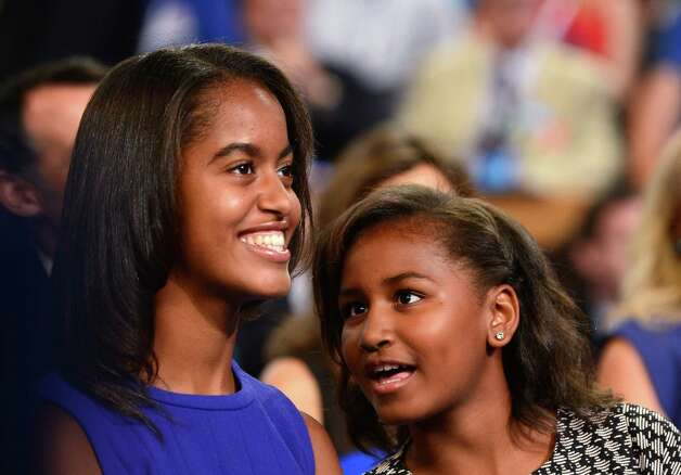 First daughters Malia and Sasha Obama confer as President Barack Obama delivers his acceptance speech for the Democratic presidential nomination at the Time Warner Cable Arena in Charlotte, N.C., on Sept. 6, 2012 Photo: ROBYN BECK, AFP/Getty Images / 2012 AFP