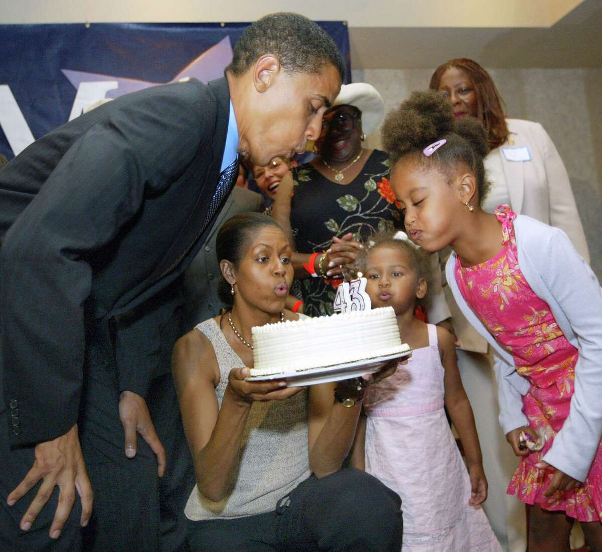 Then Senate candidate Barack Obama, D-Ill., blows out candles on his birthday cake at his 43rd birthday celebration with Michelle, who is holding the cake, and daughters Sasha and Malia during a fundraiser Aug. 4, 2004 in Matteson, Ill.