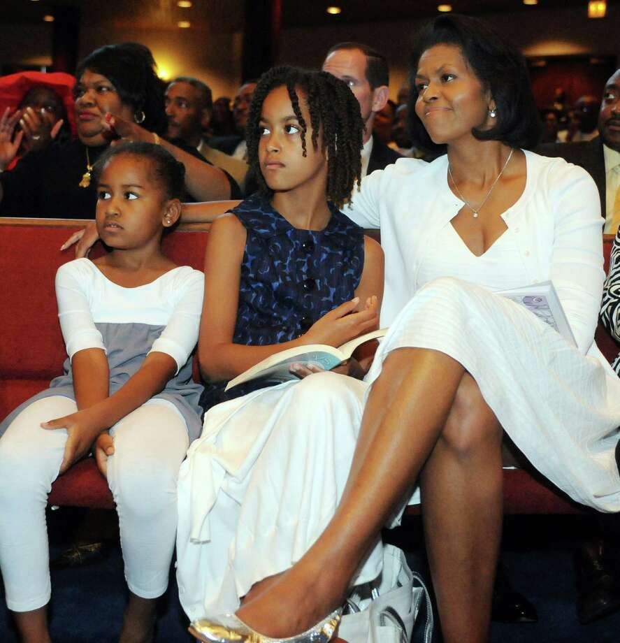 Sasha, Malia and Michelle Obama listen to Democratic Presidential hopeful Barack Obama  give a Father's Day speech at Apostolic Church of God June 15, 2008, in Chicago. Photo: David Banks, Getty Images / 2008 Getty Images