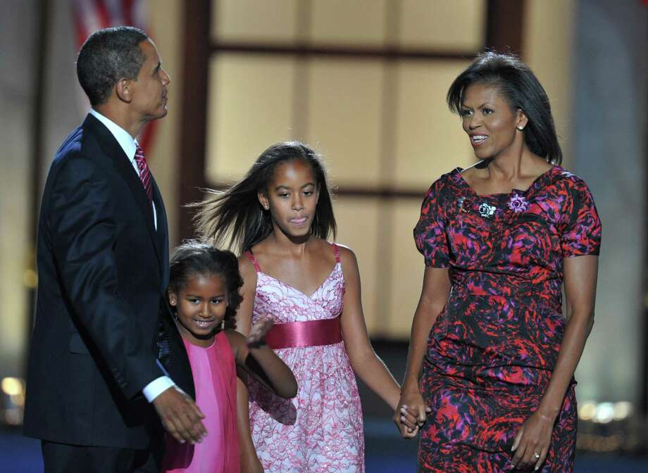 Democratic Presidential candidate Barack Obama, wife Michelle and daughters Sasha and Malia hold hands as they arrive on stage at the end of the Democratic National Convention 2008 at the Invesco Field in Denver, Colo., on Aug. 28, 2008. Photo: PAUL J. RICHARDS, AFP/Getty Images / 2008 AFP