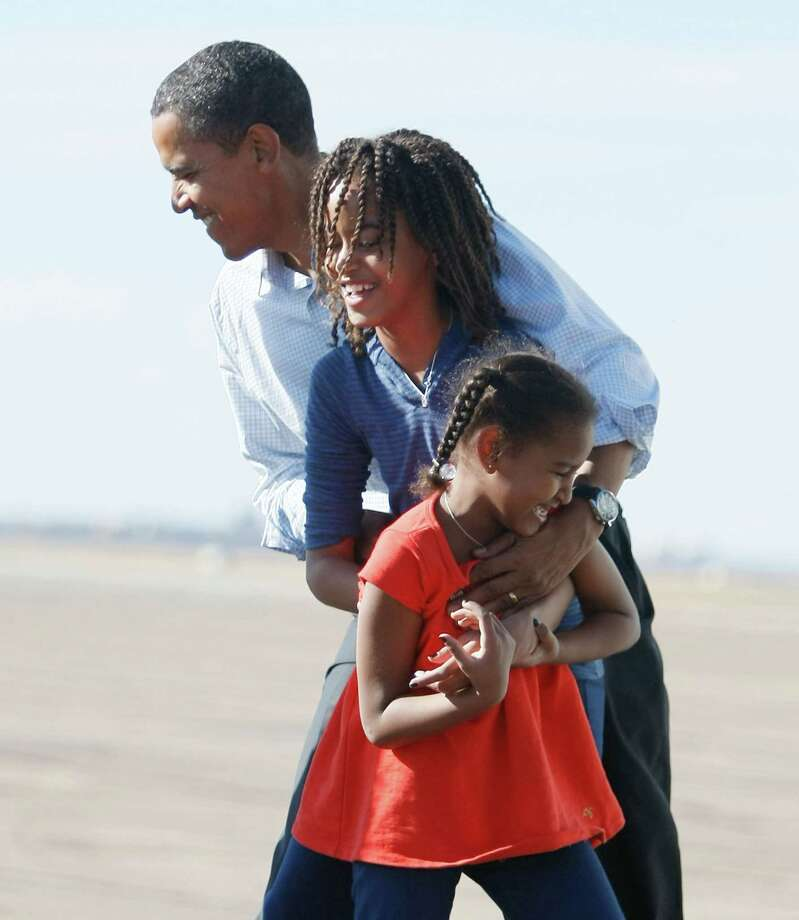 Democratic presidential nominee Barack Obama is greeted by his daughters, Malia and Sasha, after getting off his plane at Pueblo Memorial Airport Nov. 1, 2008 in Pueblo, Colo. Photo: Joe Raedle, Getty Images / 2008 Getty Images