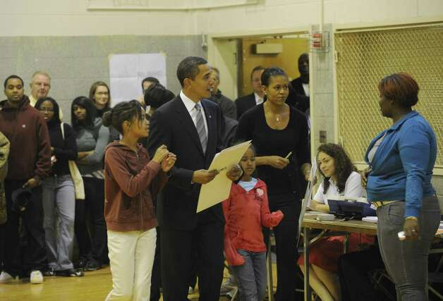 Democratic presidential candidate Barack Obama holds his ballot as he prepares to cast his vote in the 2008 presidential elections with his wife Michelle and daughters Malia and Sasha, in Chicago on Nov. 4, 2008. Photo: EMMANUEL DUNAND, AFP/Getty Images / 2008 AFP