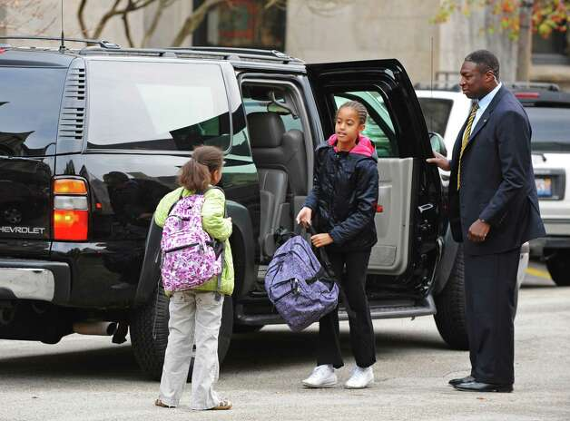 Sasha and Malia Obama are dropped off at school while their dad waits in the car Nov. 13, 2008, in Chicago. Photo: Pool, Getty Images / 2008 Getty Images