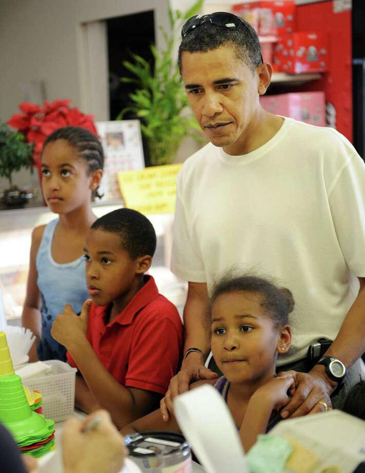 President-elect Barack Obama orders shave ice treats with his Malia and Sasha during an afternoon outing Dec. 26, 2008 ,in Hawai'i Kai, Hawaii. Photo: TIM SLOAN, AFP/Getty Images / 2008 AFP