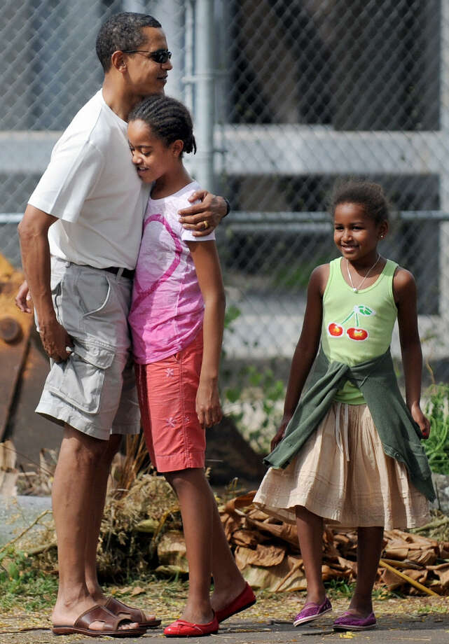 President-elect Barack Obama gets a hug from Malia, followed by Sasha, as they meet at the Honolulu Zoo Dec. 30, 2008, in Honolulu, Hawaii. Photo: TIM SLOAN, AFP/Getty Images / 2009 AFP