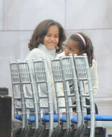 "Malia and Sasha Obama wait for the start of the 'We Are One"" concert, one of the events of President-elect Barack Obama's inauguration celebrations, at the Lincoln Memorial in Washington, D.C. on Jan. 18, 2009. Photo: JEWEL SAMAD, AFP/Getty Images / 2009 AFP"