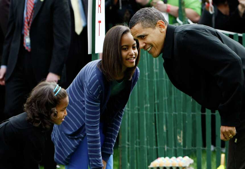 President Barack Obama checks on his daughters, Malia and Sasha, before the start of the White House