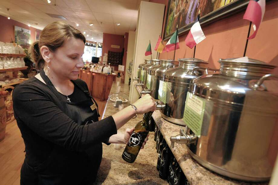 Barbara Braidwood, one of the co-owners of Saratoga Olive Oil Co. pours some Chilean koroneiki extra virgin olive oil out of a stainless steel fusti and into a bottle at the store on Tuesday, Oct. 30, 2012 on Broadway in Saratoga Springs, NY.  The store sells different flavors of olive oil, balsamic vinegar and salt.   Barbara along with her husband Clint Braidwood and his brother Chad Braidwood, own and operate the store.  (Paul Buckowski / Times Union) Photo: Paul Buckowski