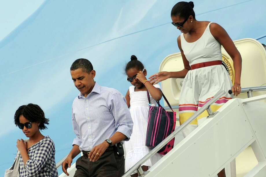 President Barack Obama, First Lady Michelle Obama and their daughters, Malia and Sasha, leavefrom Air Force One at the Cape Cod Coast Guard Air Station on Martha's Vineyard on Aug. 23, 2009. Photo: JEWEL SAMAD, AFP/Getty Images / 2009 AFP
