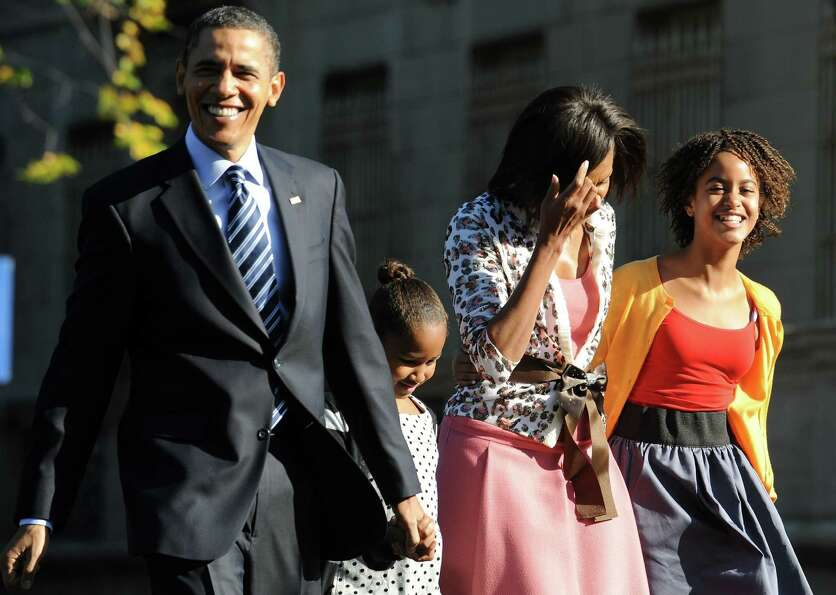 President Barack Obama, Malia, Michelle and Sasha walk back to the White House after attending a pra
