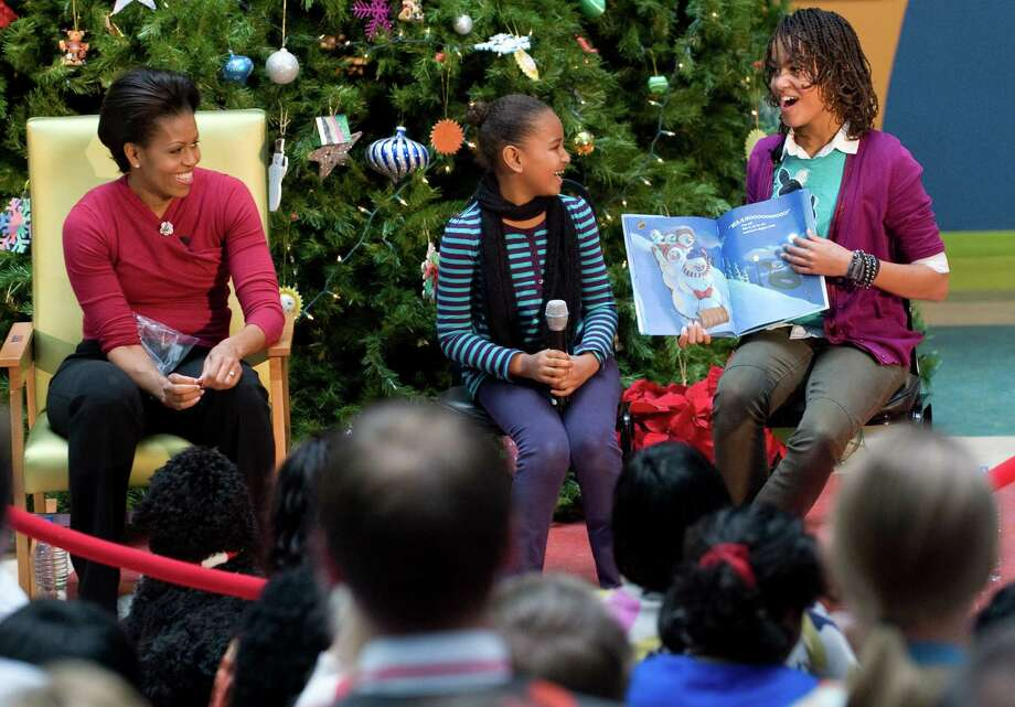 "Malia Obama reads the book ""Snowmen at Night,"" by Caralyn Buehner, with sister Sasha and mom Michelle, during a visit to the Children's National Medical Center in Washington, D.C., on Dec. 22, 2009. Photo: SAUL LOEB, AFP/Getty Images / 2009 AFP"
