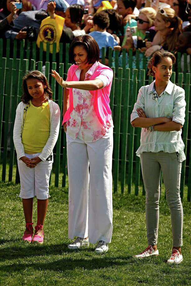 First lady Michelle Obama waves to guests while standing with her daughters Sasha, 8, and Malia, 11, during the Easter Egg Roll at the White House April 5, 2010, in Washington, D.C. Photo: Chip Somodevilla, Getty Images / 2010 Getty Images
