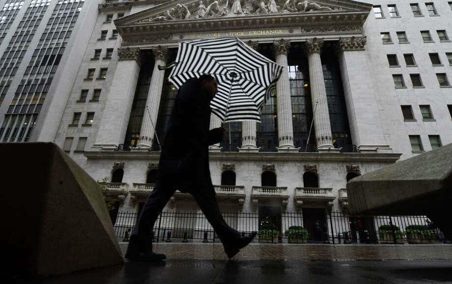 A pedestrian walks past the New York Stock Exchange the day after Pres. Barack Obama was re-elected, Wednesday, Nov. 7, 2012 in New York. A new storm that threatened to complicate Hurricane Sandy cleanup efforts on Wednesday now looks like it will be weaker than expected.  Winds could still gust to 50 mph in New York and New Jersey Wednesday afternoon and evening. Photo: Henny Ray Abrams, AP / FR151332