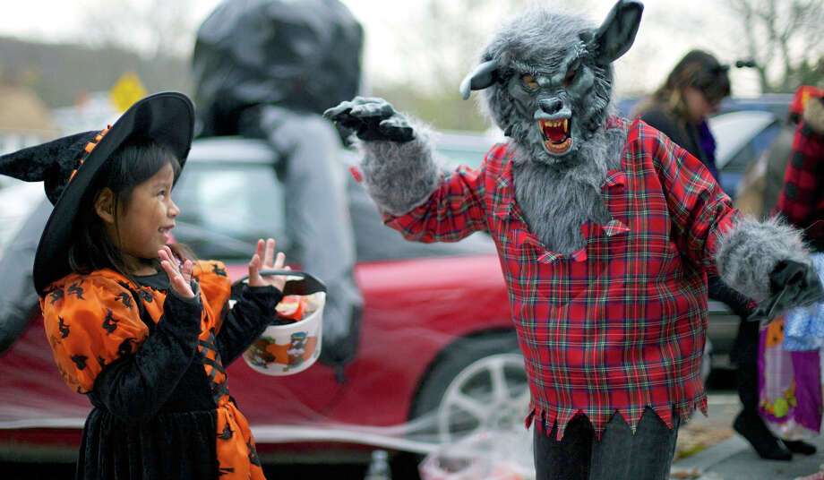 Even young witch Lizzy Tietjen, 5, of New Milford  appears somewhat afright at the sight of her brother, Nate, 7, enthusiastically acting the role of a fearsome werewolf during New Milford Parks & Recreation's Halloween celebration called Trunk or Treat on the Village Green. Oct. 31, 2012 Photo: Norm Cummings