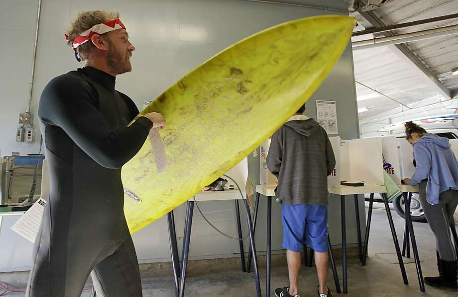 """Totally stoked by the democratic process:Mike Weigard carries board and ballot to the ballot box after voting at the Venice Beach lifeguard headquarters in Los Angeles. """"It's awesome the polling place is where I surf,"""" says Mike. Photo: Reed Saxon, Associated Press"""