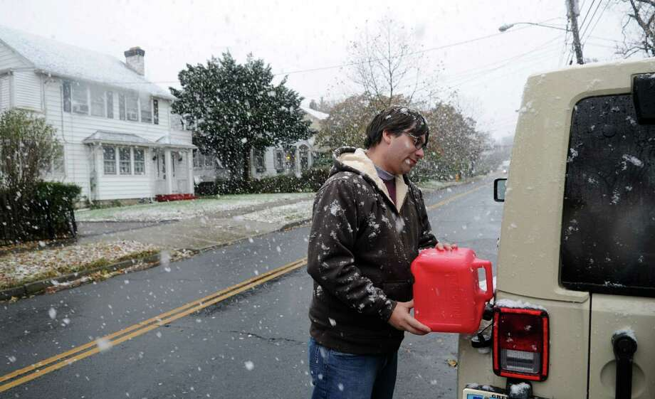 Andrew Schnelwar fills his car with gasoline left over from the generator he used during Superstorm Sandy as snow begins to fall from a nor'easter in Stamford, Conn., on Wednesday, November 7, 2012. Photo: Lindsay Niegelberg / Stamford Advocate